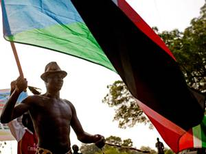 A Southern Sudanese man carries a national flag